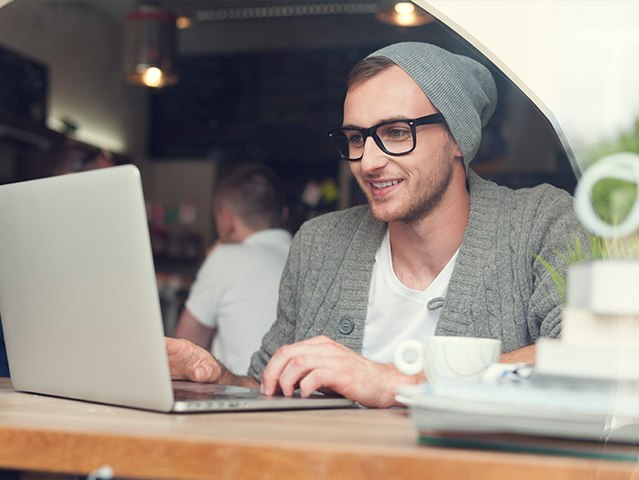 man with hat sitting at laptop